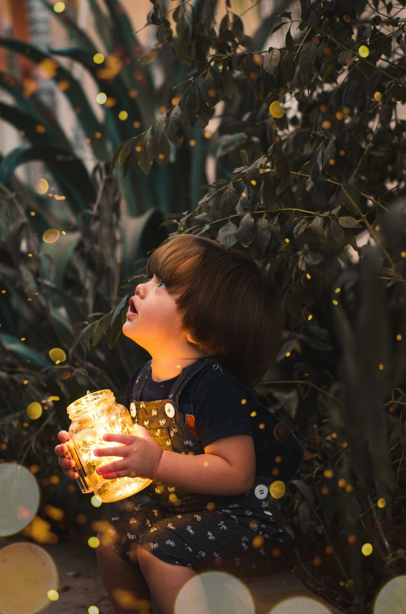 Child by an indoor plant