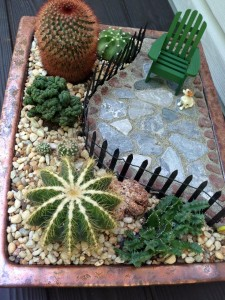 Miniature garden with planting, paving, seating, cactus and fencing