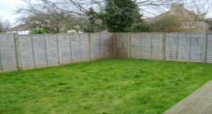 A boring garden with lawn and fences no planting
