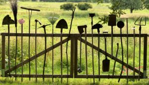 a garden gate with spades, rakes and garden tools overlooking green countryside