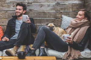 Two people with a dog all looking happy and enjoying outdoors with a cup of tea