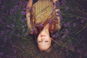 a healthy and happy person laying down in the garden surrounded by blue lavender