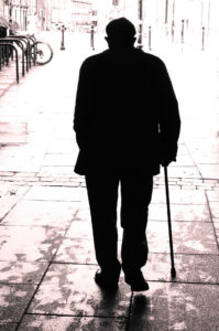 old man walking down the street looking lonely