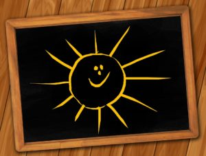 Blackboard showing a cartoon sunshine with a face