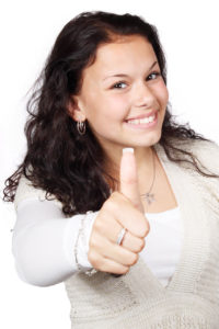 lady looking happy and doing a thumbs up signal because she has kept her near year's resolutions