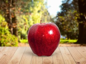Red apple placed on a table out in a garden.