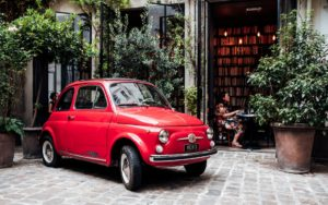 A French courtyard with a Fiat car, surrounded by huge pots filled with evergreen plants.