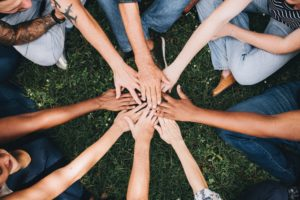 a group of people outdoors uniting their hands