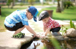 two boys playing by the edge of a pond during pond dipping