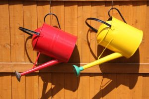 a red and yellow watering can hanging on a timber fence