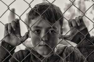 child looking through a wire chain link fence