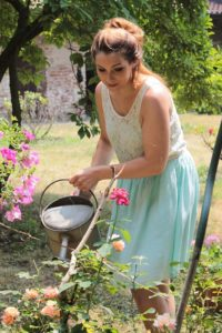 lady watering her rose bushes using a watering can