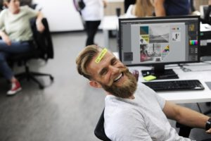 man in office laughing, happy