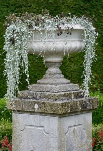 A stone urn on a plinth in a garden